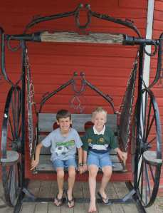 Boys in wheeled swinging chair old time town