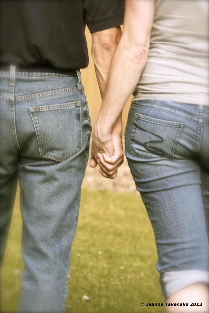 a photo taken from the back of a man and woman holding hands