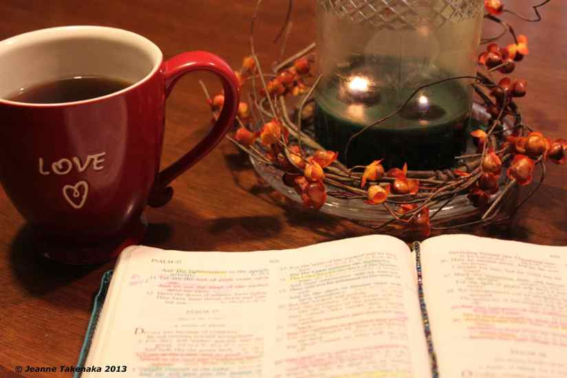 A picture of an open Bible, a red mug of coffee an a lit candle.