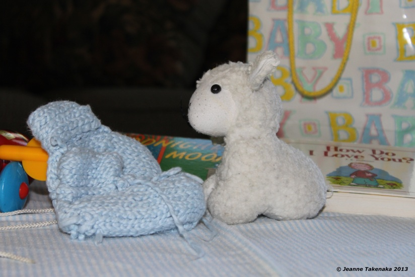A lamb, a knitted baby bootie and a couple of baby toys