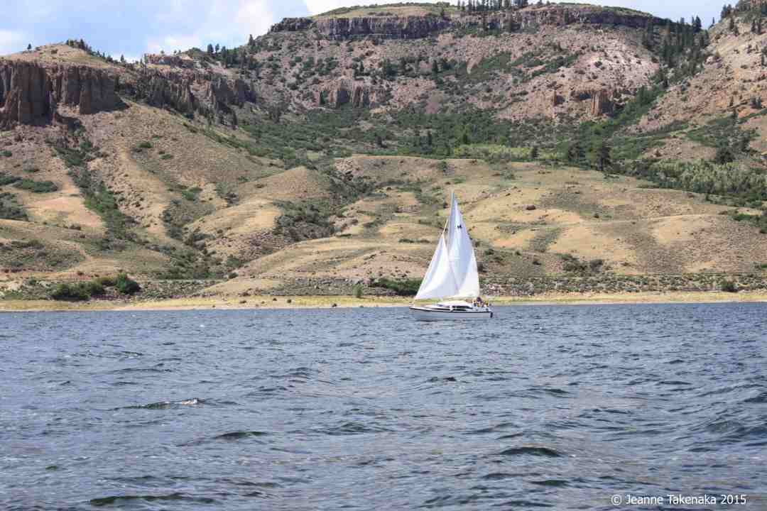 Image of a sailboat sailing with a mountain-y backdrop