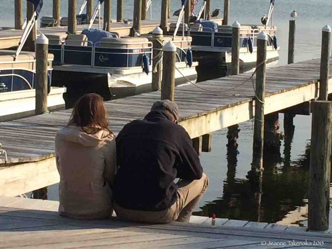 A photo of a couple sitting on a dock and facing the water