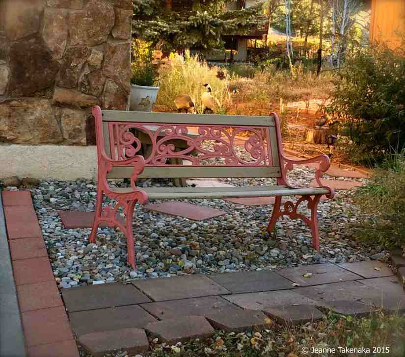 A bench sitting near a paving stone walkway with fall colors in the background