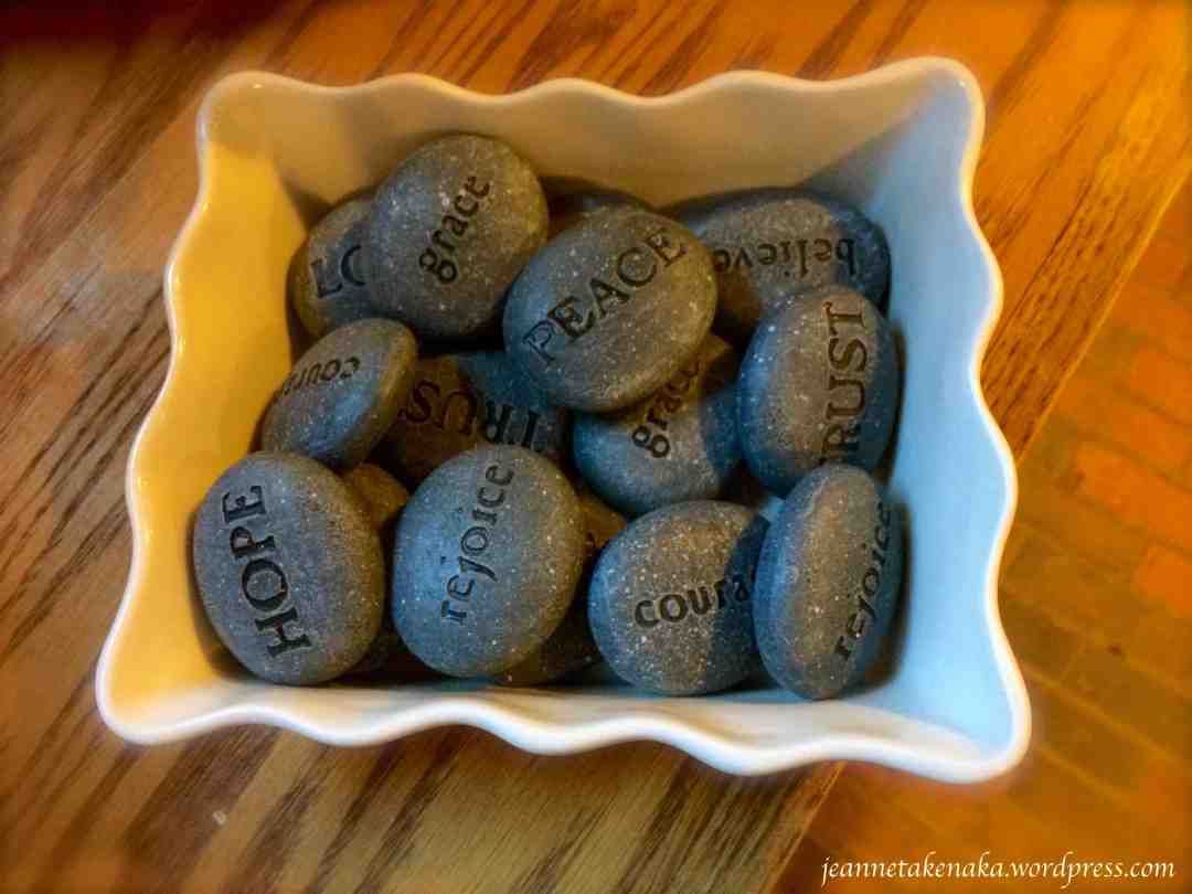 "A bowl of ""word rocks"" with encouraging words like hope, peace, trust, believe, rejoice, courage"
