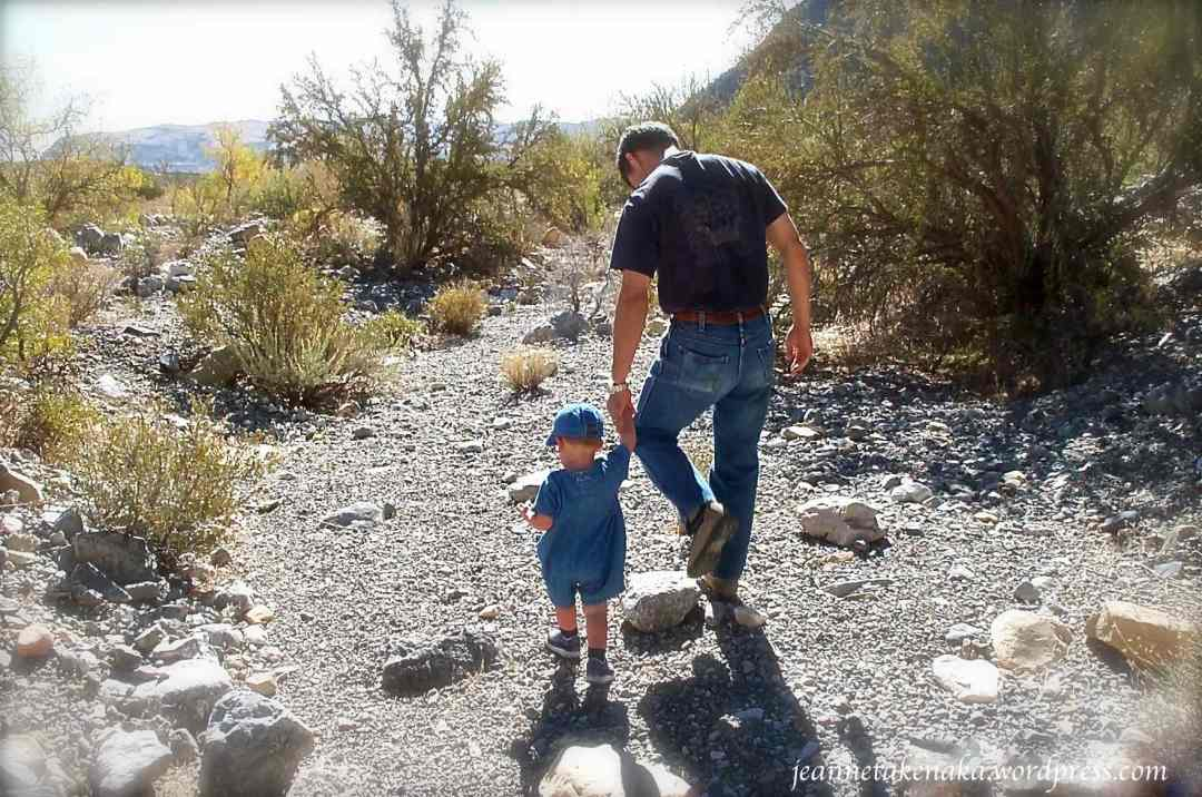 A man walking with a young toddler