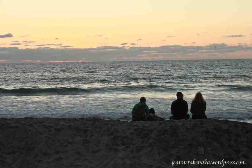 A man, woman and children sitting on the sand near the ocean at sunset