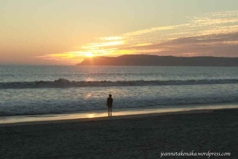 A person standing on the shore and watching the sun go down behind an island
