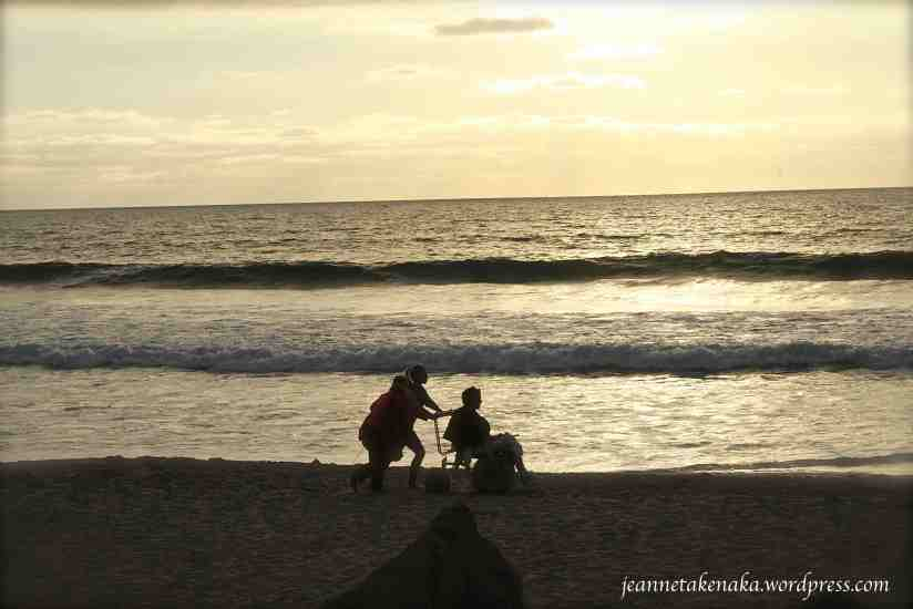 Two young women pushing a boy in a wheelchair on the beach at sunset