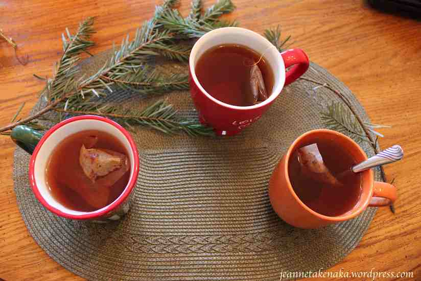 Image of three mugs of tea on a place mat with pine bows
