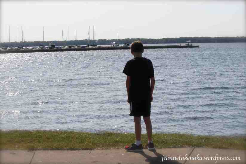 The silhouette of a boy staring out at a large lake