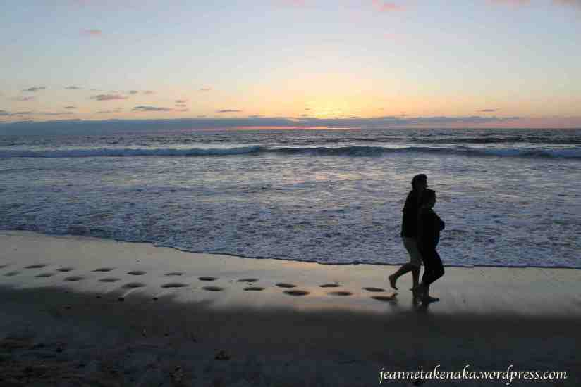 A husband and wife walking on the beach at sunset, their footprints trailing behind them on the wet sand