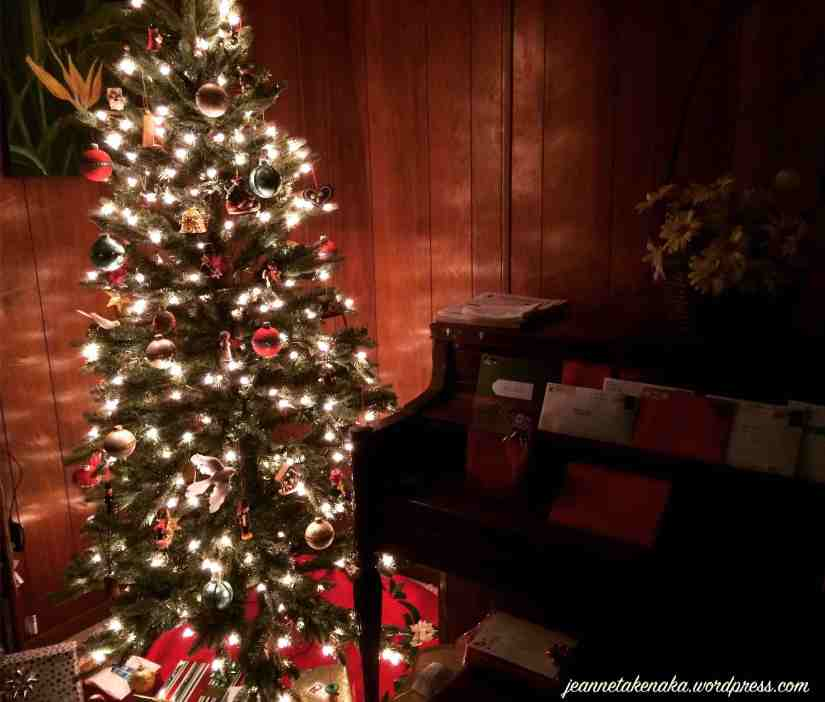 A lit Christmas tree in dim room casting light on the walls