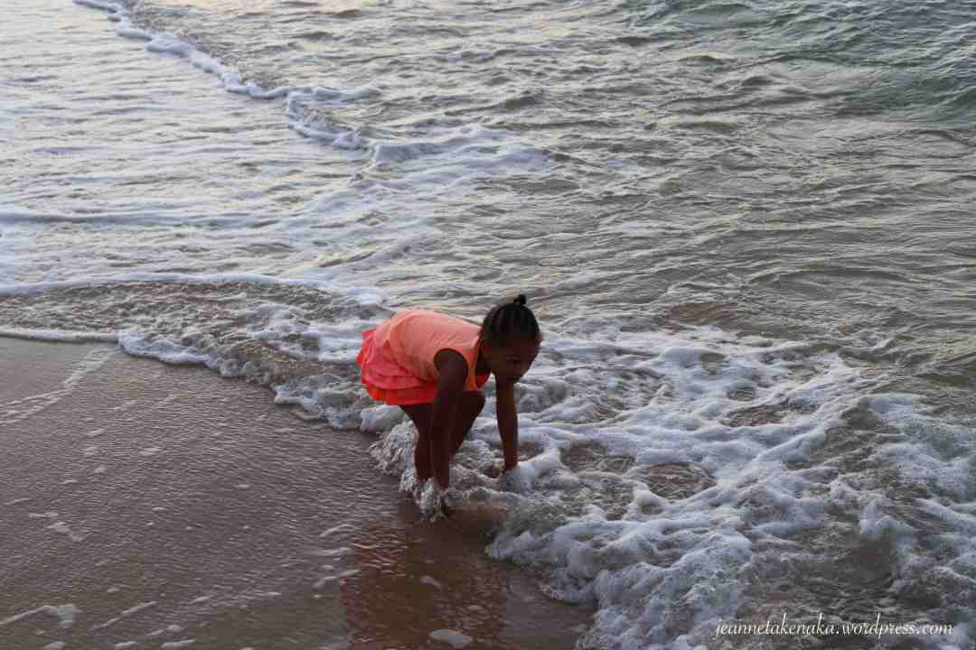 A small girl playing in small waves on the beach