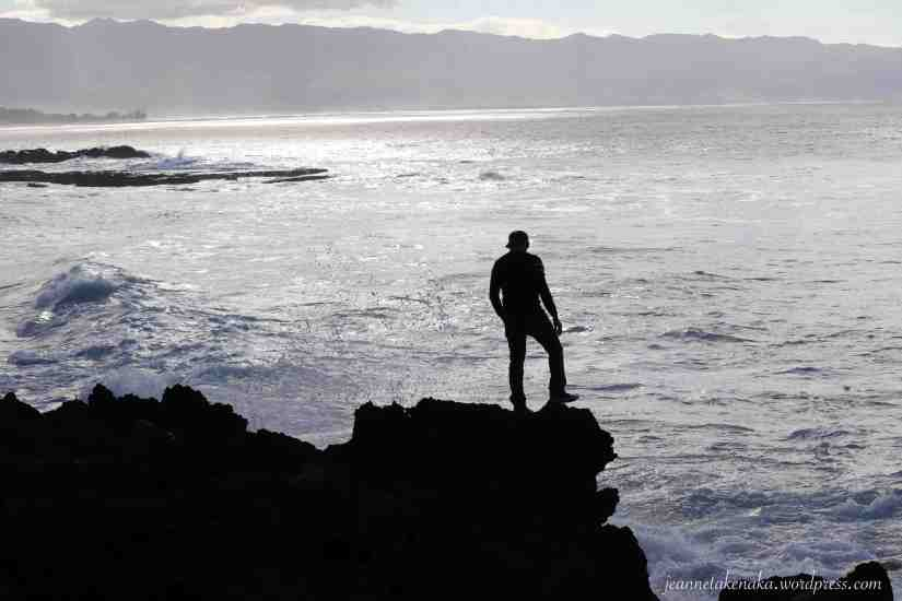 The silhouette or a man standing on rocks and watching the waves churn below him.