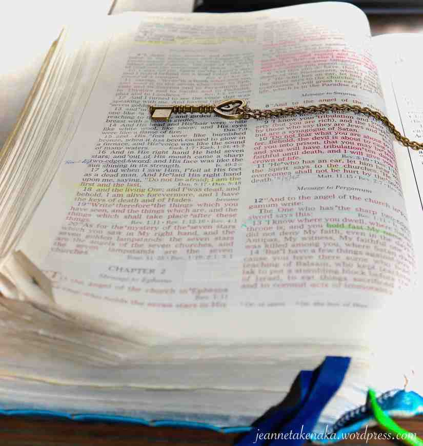 A Bible with a key on a chain laid across the open page
