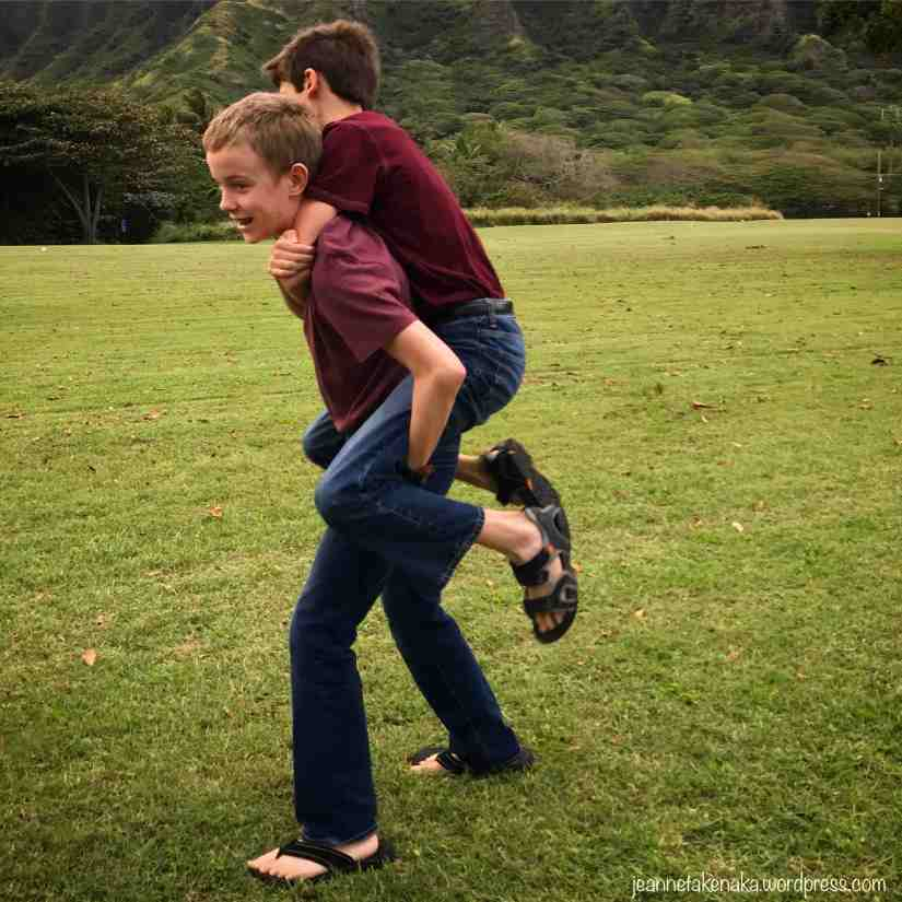 Two teen boys, one giving the other a piggy back ride