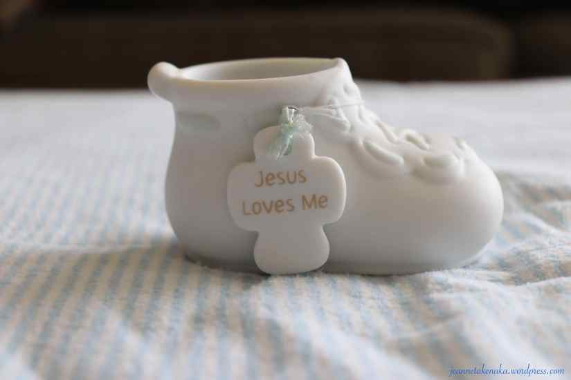 "A porcelain baby bootie with a cross that says, ""Jesus loves me"""