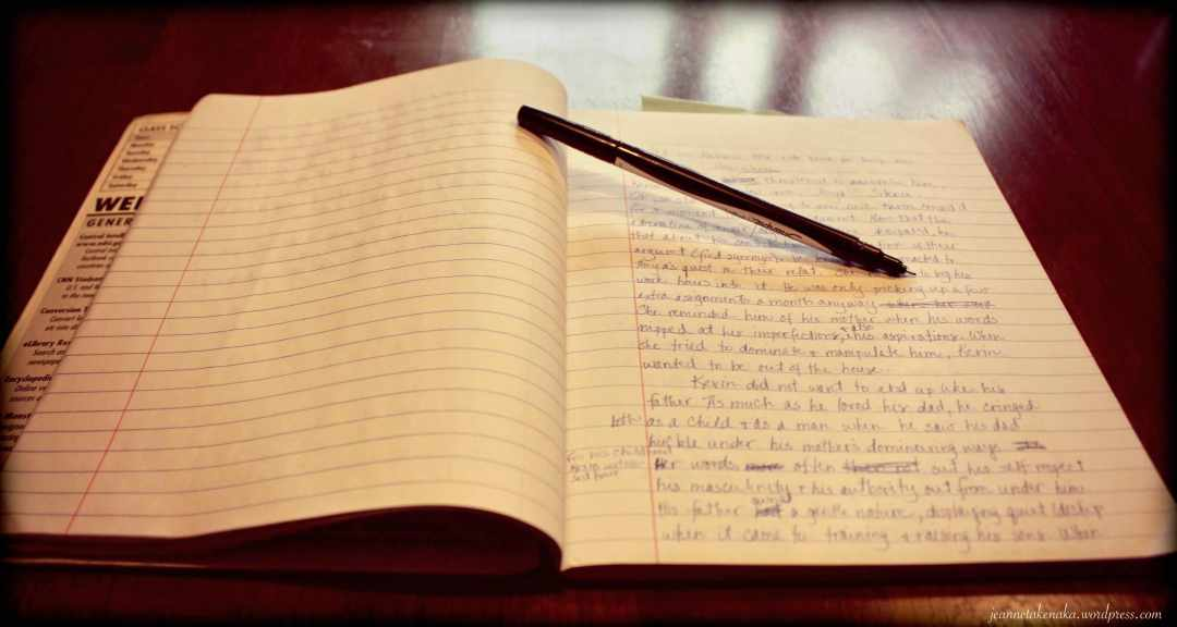 A picture of a journal with hand writing and scribbles and a pen propping open the pages