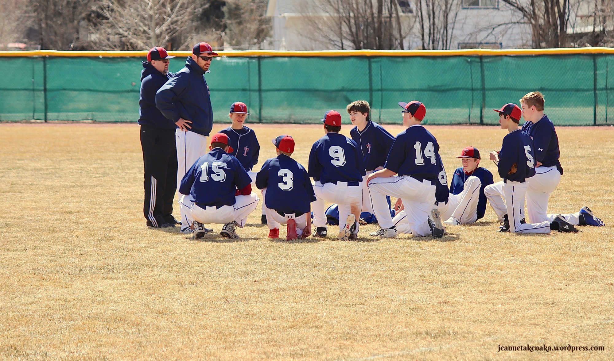 Perspective: Team gathered around coaches after baseball game