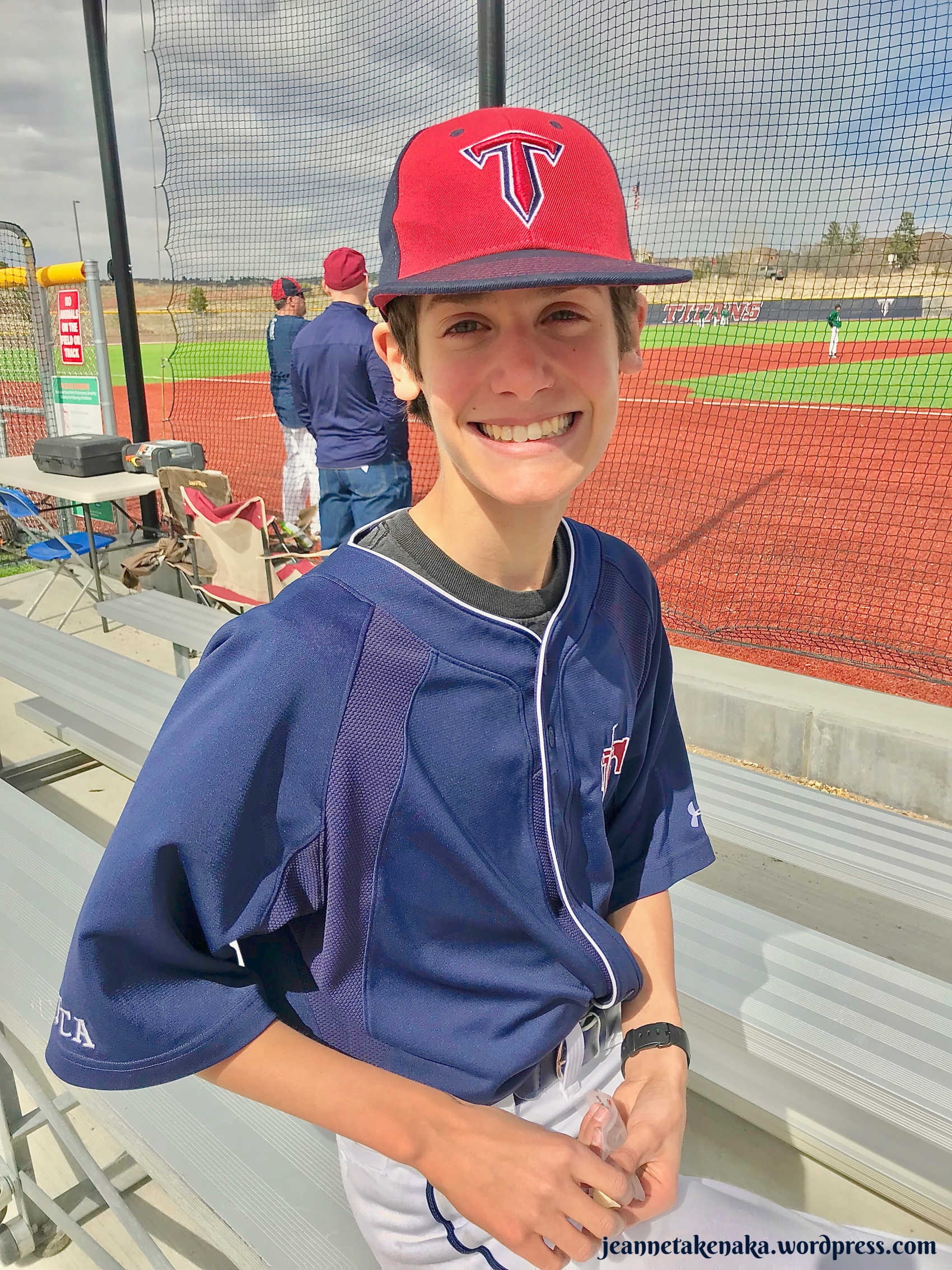 Perspective: Peter sitting on the bleachers in his baseball uniform posing for a photo