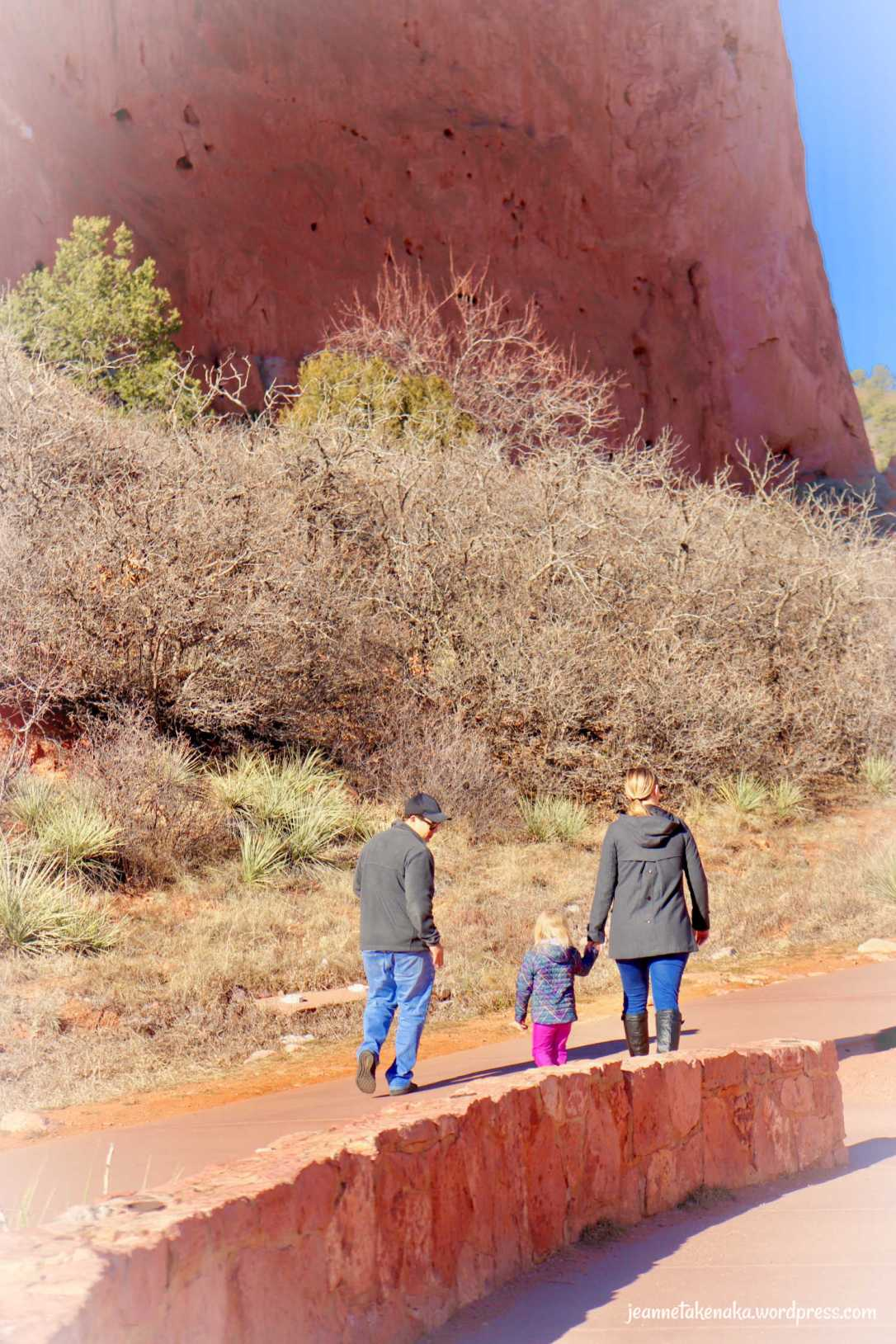 A man and a woman walking with a small child, the woman holding the child's hands