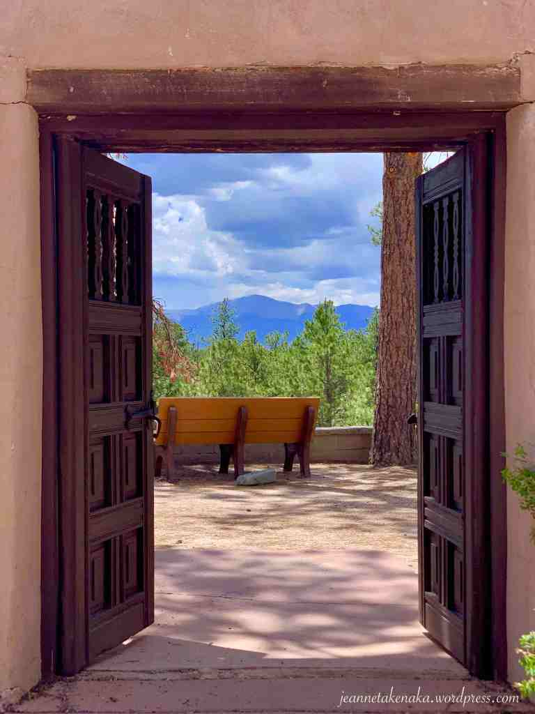 A picture of outside wooden doors opening to a summery scene with trees and mountains on the other side