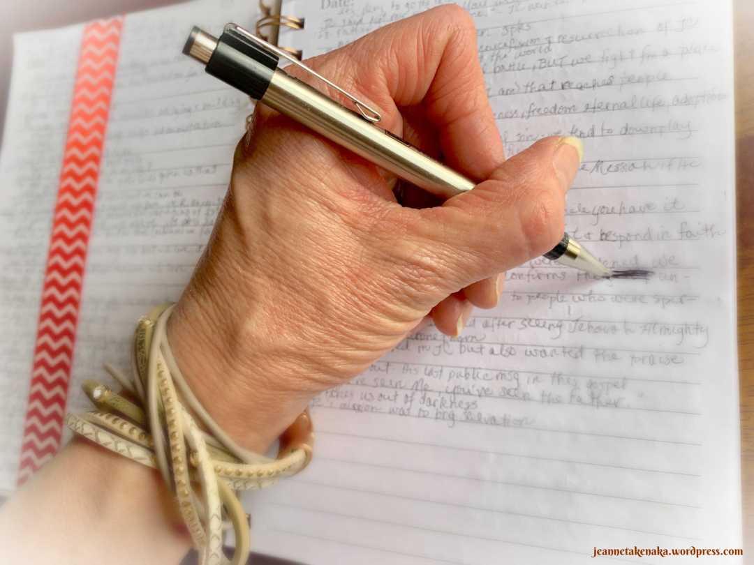 A hand writing in a journal and scratching something out