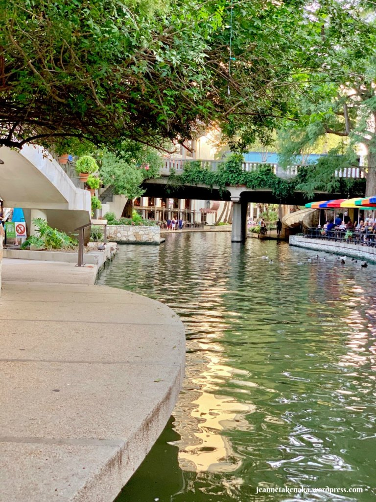 The Riverwalk canal with ducks and a bridge and umbrellas on the right