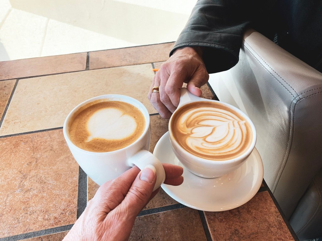 Two cups of coffee with two different hands holding the handles