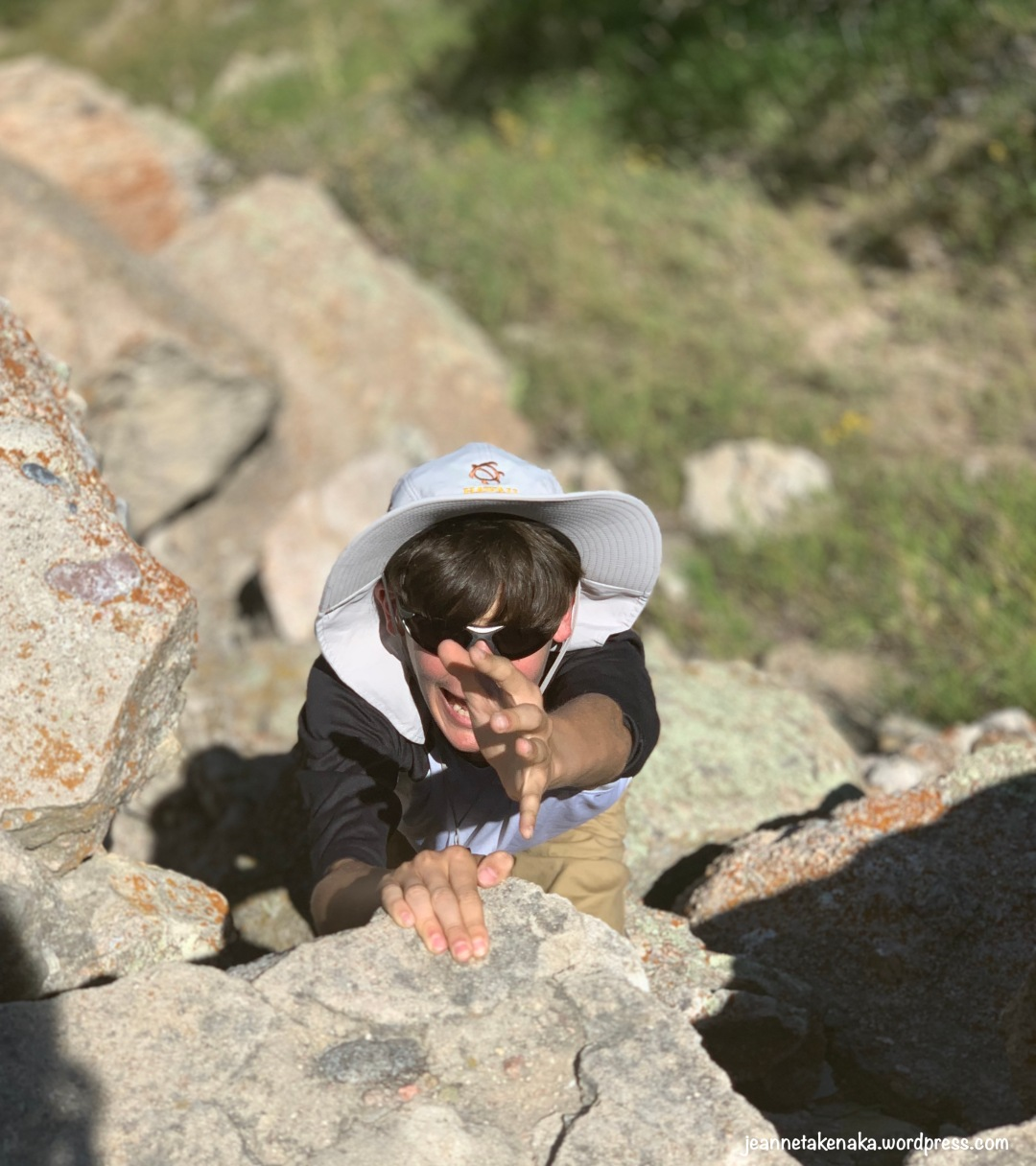 A young man hanging from rocks and holding one hand up for help