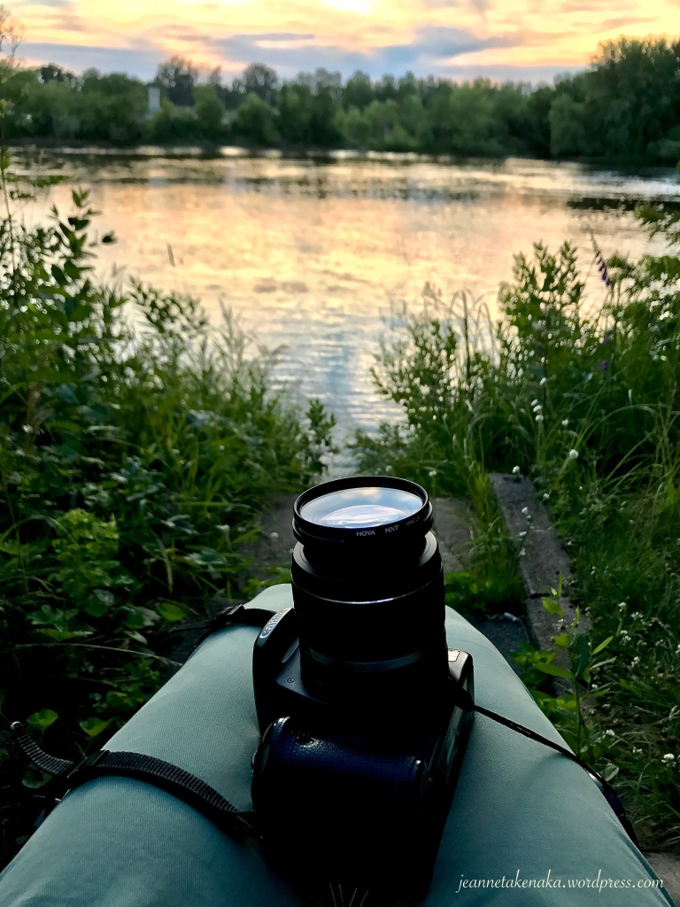 A woman sitting next to a lake at sunset with a camera and lens exposed on her lap, reminding one to focus