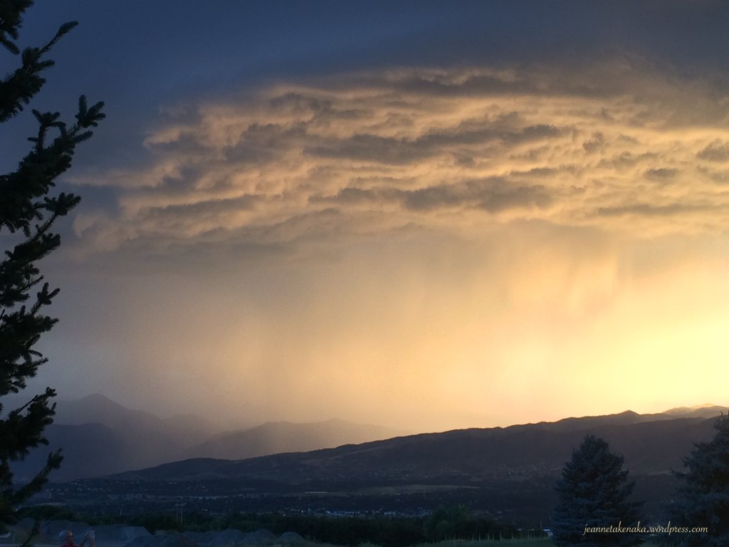 A stormy sky with rain falling at sunset