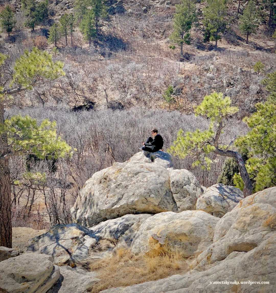 A teen boy sitting on the edge of a rocky overhang