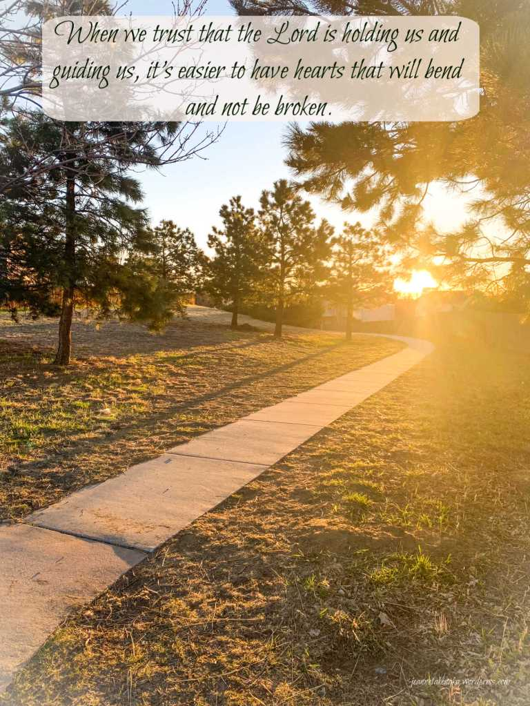 "Meme with these words: ""When we trust that the Lord is holding us and guiding us, it's easier to have hearts that will bend and not be broken."" on a backdrop of a sun-streaked path"