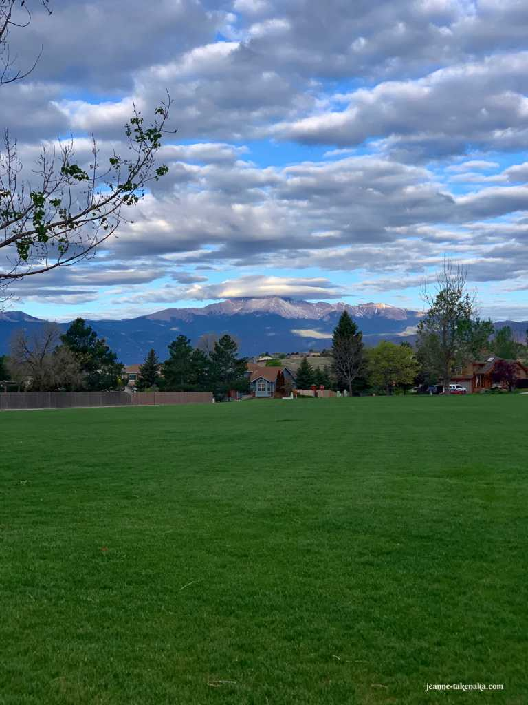 An empty park with a view of a mountain crowned with a cloud