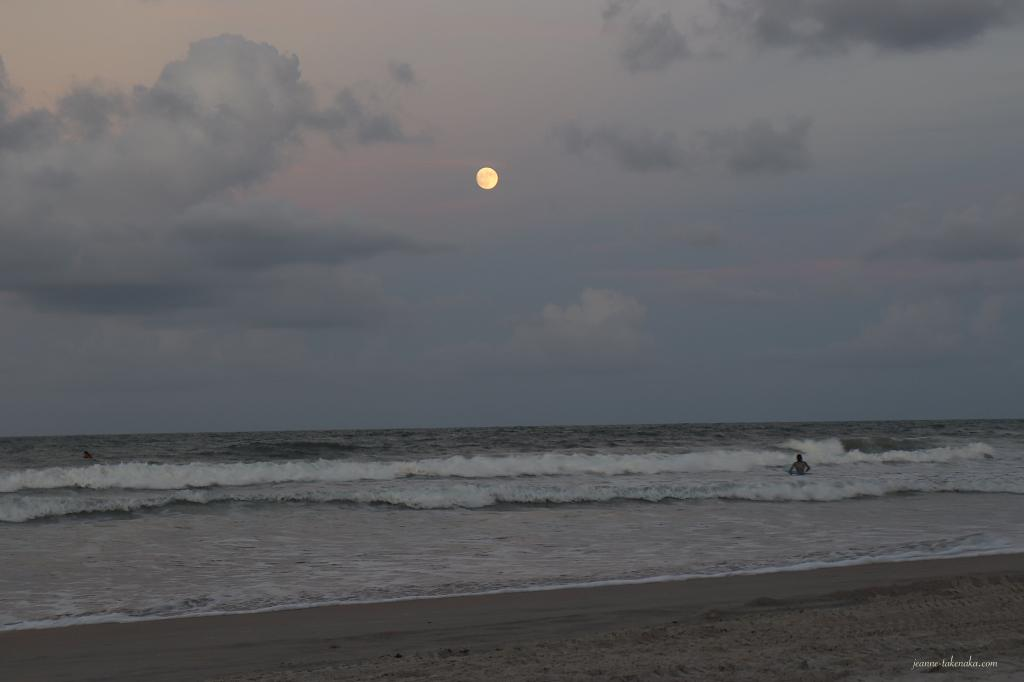 Picture of the moon rising above the ocean