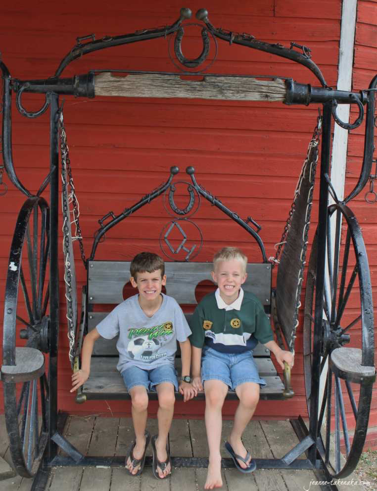 Two boys sitting on a swing together