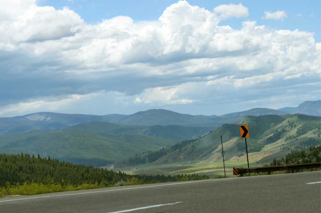 An image of a curving mountainous road with a sign indicating to curve right