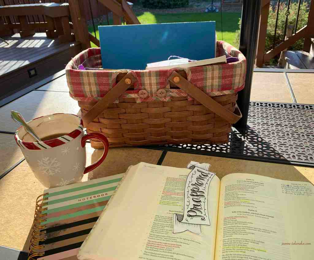 An outdoor scene of a Bible, coffee, and a basket outdoors on a summer morning